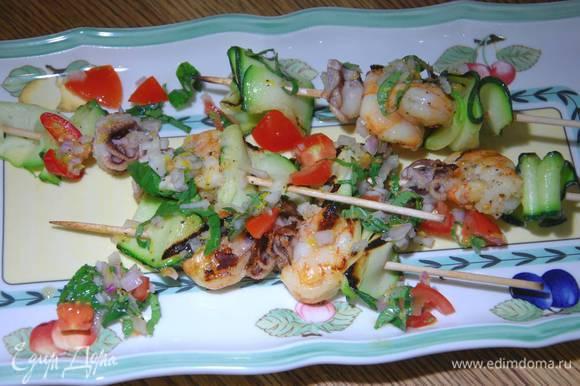 Выложить на блюдо шпажки с морепродуктами, а сверху соус.