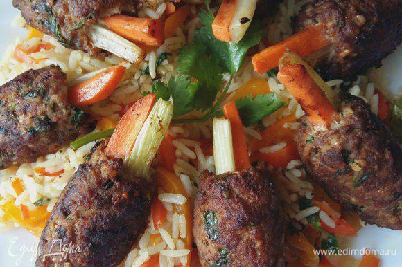 Выкладываем горкой на блюдо рис с овощами, сверху укладываем наши котлетки.