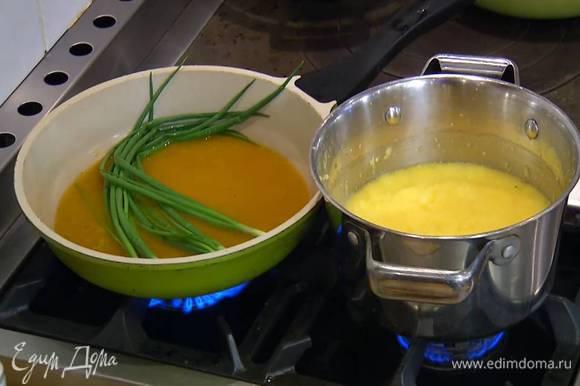 В ту же сковороду влить соус с шафраном, выложить перья зеленого лука и слегка припустить его на небольшом огне.