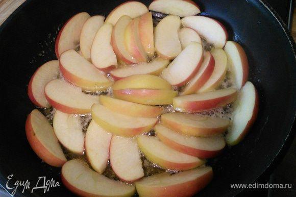 Выложить яблочные дольки, посыпать по вкусу корицей и обжарить до легкой карамелизации.