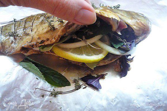 По истечении времени рыбу укладываем на лист фольги, в брюшко кладем дольки лимона, кольца лука, лавровый лист, листики мяты и базилика. Сверху посыпаем солью, перцем и тимьяном.