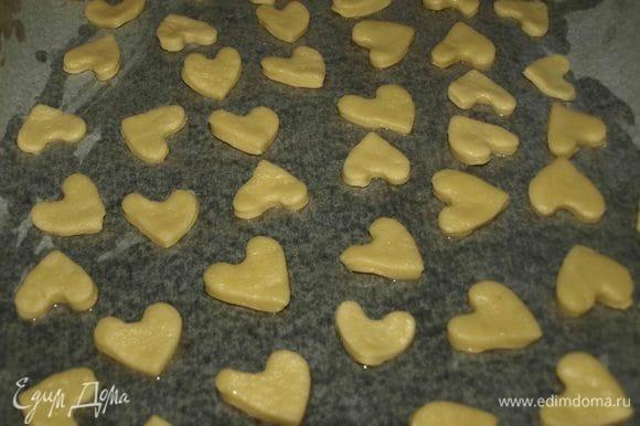 Остатки теста раскатать, вырезать печенья. На противень выстелить пекарскую бумагу, смазать растительным маслом. Печенья выкладываем на противень и отправляем в духовку, разогретую до 180°С, на 10-12 минут.