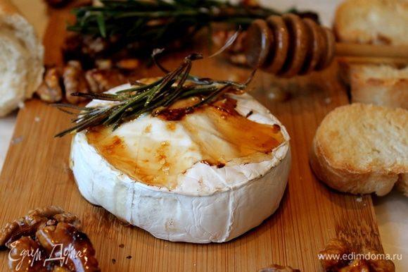 Спустя 15 минут, когда вы почувствуете, что сыр внутри стал мягким, а мед начал превращаться в карамель, аккуратно перенесите его на дощечку, разложите карамелизированные орехи и ломтики багета.