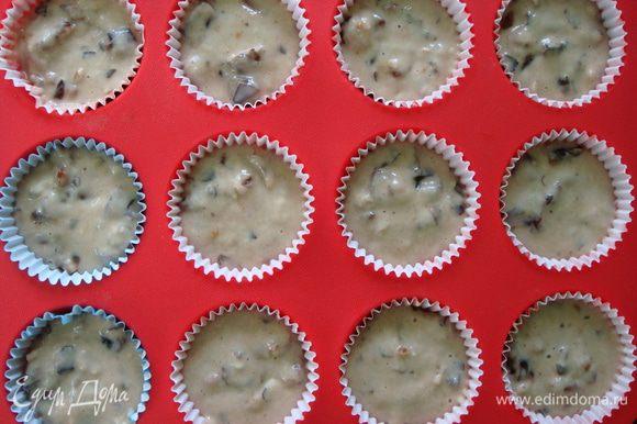 В силиконовые формочки для кексов вложить бумажные капсулы. Выложить в них тесто на 3/4 и поставить в разогретую до 180°С духовку на 25-30 минут. Готовность проверить зубочисткой.