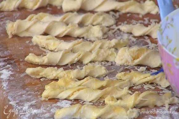 Посыпать тесто оставшимся пармезаном, нарезать длинными тонкими полосками, сложить каждую вдоль пополам сыром внутрь и скрутить спиралькой, сверху смазать желтком с молоком.