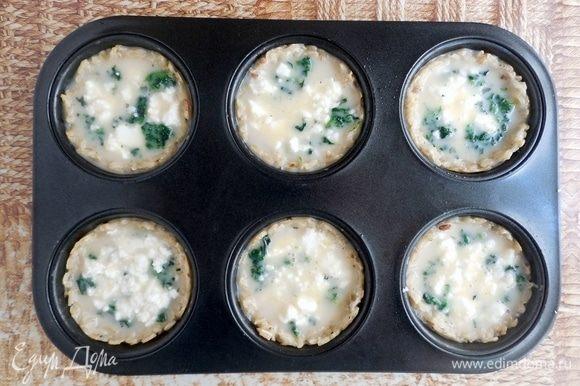 Шпинат и сыр поровну распределить между остывшими основами. Затем залить яичную смесь. Выпекать 15 мин.
