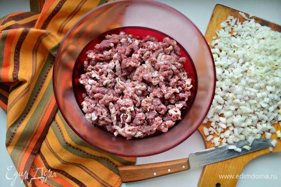 Лучше порубить мясо тяжелым ножом, но, если такой возможности нет, то пропустить мясо через мясорубку с крупными отверстиями. Лук мелко порубить.
