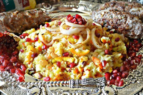 Подавать готовый рис-плов с люля-кебабами, зернами граната и поджаренным луком.