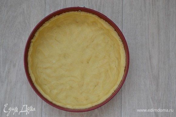 Достать тесто из холодильника, форму смазать маслом, выложить тесто в форму, делая бортики. Либо можно раскатать тесто на рабочей поверхности, присыпав мукой, вырезать круг по форме, прибавляя к диаметру несколько см для бортиков, и перенести с помощью скалки в форму.