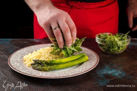Выложите кускус со спаржей порционно в тарелки, сверху положите руколу и полейте блюдо оливковым маслом.