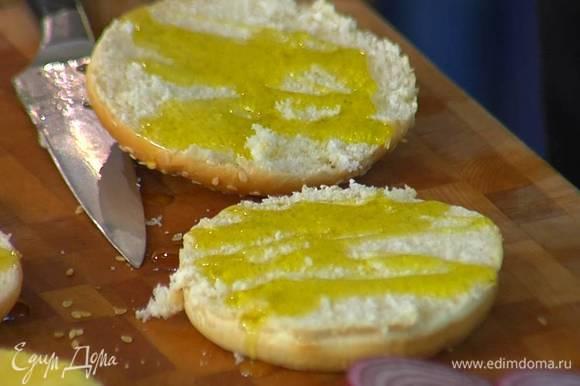 Булочки разрезать пополам вдоль и сбрызнуть срезы оливковым маслом Extra Virgin.