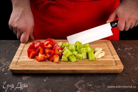 Красный болгарский перец и огурец почисить, нарезать кубиками. Чеснок раздавить плоской стороной ножа.