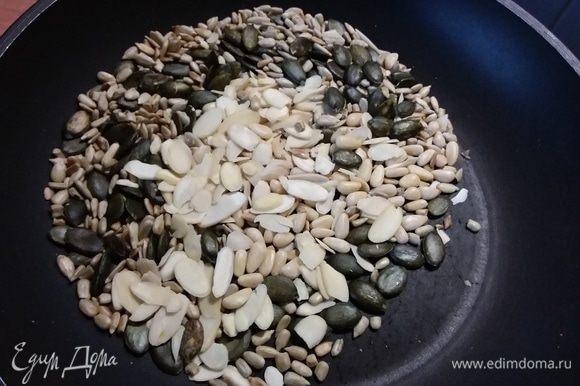 В отдельной сковороде соединить семечки, орешки и миндальные лепестки, обжарить.