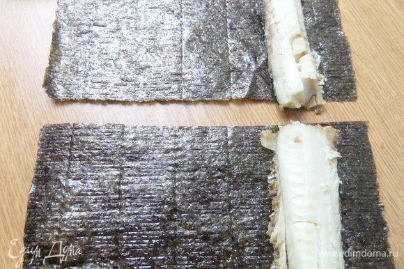 Второй лист нори делим пополам. Положить с краю филе хека.