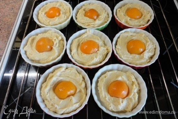 Если формочки не силиконовые, то лучше их смазать растительным маслом и посыпать сухарями или манной крупой. Выложить тесто, а в середину по половинке абрикоса.