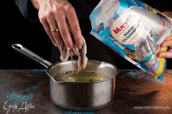 Налить в кастрюлю воды, добавить перец горошком, лавровый лист, одну очищенную луковицу. Довести воду до кипения. Разморозьте мини-осьминогов ТМ «Магуро» и положите в кипящую воду. Варите 15 минут до готовности. Готовых мини-осьминогов остудите в той воде, в которой они варились.