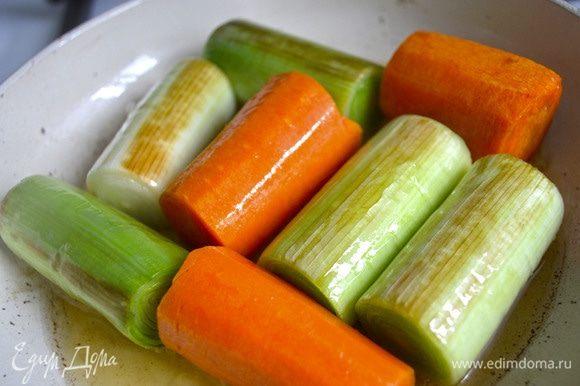 У порея удалить внешние листья, с моркови снять внешний слой, с долек чеснока снять шелуху. Налить в сковороду оливковое масло, обжарить овощи, переворачивая, со всех сторон до золотистой корочки.