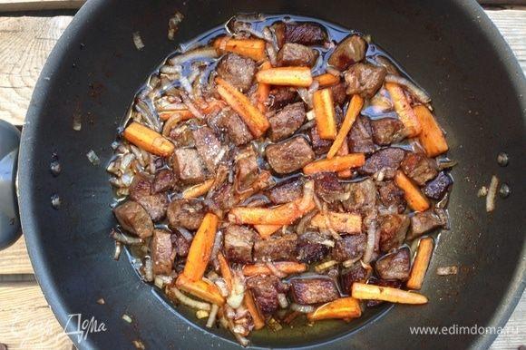 Вернуть в сковороду мясо, добавить специи, влить 1 стакан кипятка, накрыть крышкой, убавить огонь и готовить зирвак 45-50 минут.