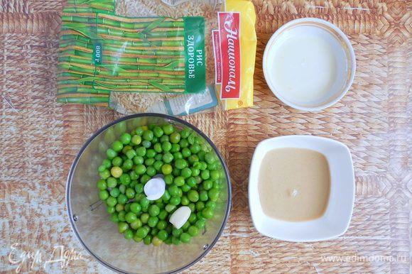 Слить холодную воду с горошка. В чашу блендера поместить горошек, лимонный сок, чеснок и тахини. Измельчить до однородности. Если масса будет слишком густой, добавьте немного воды от варки горошка (остывшей).