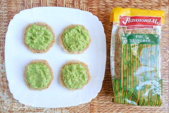 Остывшие крекеры аккуратно отделить от бумаги. 8 крекеров перевернуть и распределить поровну между ними зеленый хумус.