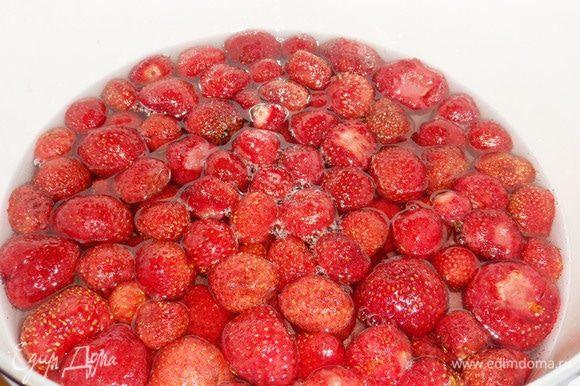 Оставшийся сахар смешать с водой. Поставить на огонь, как только сахарный песок полностью растворится, опустить ягоды клубники в сироп. Варить на слабом огне (сироп должен «шептать») около 10 минут.