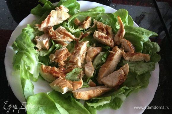 Куриную грудку нарежьте тонкими полосками и выложите на листья салата.