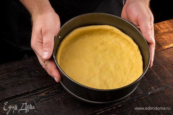 Тем временем приготовьте начинку. Крыжовник переберите, промойте тщательно и обсушите. Смешайте ягоды с оставшимся сахаром. Обомните тесто, раскатайте тонким слоем и выложите в форму диаметром 26 см, оставив бортики.