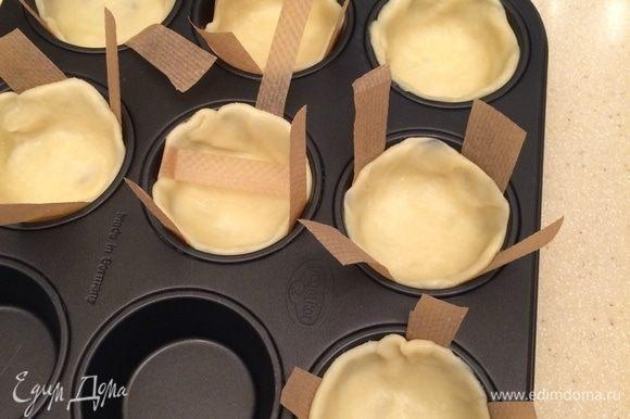 Тесто раскатать в тонкий пласт, вырезать круги, уложить в металлическую форму для выпечки маффинов.