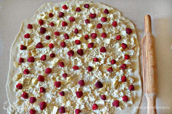 Охлажденное тесто выложить на присыпанную мукой поверхность, раскатать в прямоугольник и смазать растительным маслом. Выложить на тесто творожно-грушевую начинку, оставляя края на 2 см свободными, сверху равномерно распределите ягоды малины и кусочки сливочного масла.