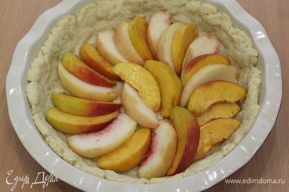 Вынуть форму, уложить порезанные дольками персики.
