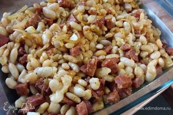 В форму для запекания выложить лук с чоризо, смешать с отварной фасолью, выложить крупно порезанные кусочки чеснока.