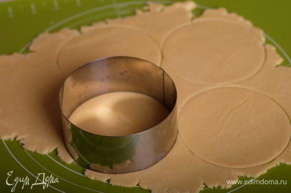 Раскатать тесто (сверху положить пергамент, так тесто не будет прилипать к скалке) до толщины 2-3 мм и круглыми вырубками вырезать круги, диаметром на 2-3 см больше, чем внутренний диаметр формочек для тарталеток.