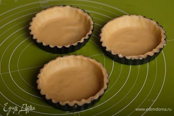 Далее уложить круги в формочки для тарталеток, аккуратно прижимая ко дну и краям формы. Излишки теста обрезать. Поместить формы с тестом в холодильник еще на час. За это время хорошо разогреть духовку до 180°С.