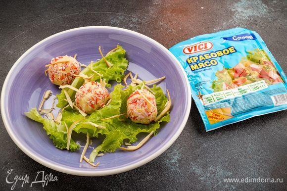 Обваляйте в крабовой крошке закусочные шарики. Подавайте на листьях салата. Приятного аппетита!