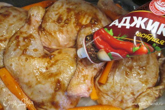 Нагреваем духовку до 200°С. Форму для запекания смазываем растительным маслом и укладываем на дно сначала лук, кусочки моркови. Сверху кладем куриные окорочка, между ними — морковь. Дополнительно окорочка можно еще смазать аджикой.