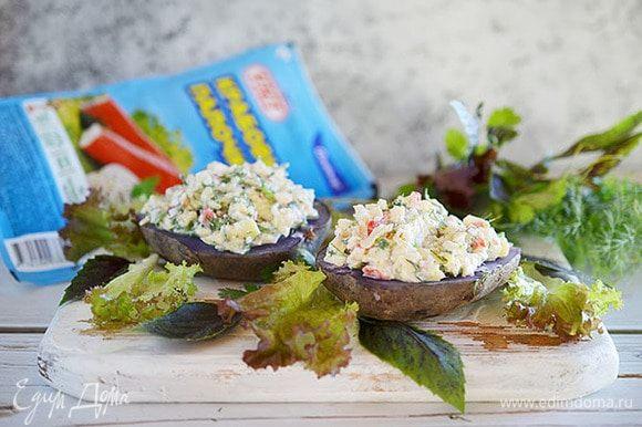 Выложить на половинки картофеля салат.