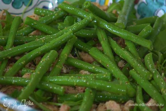 Готовую кенийскую фасоль полить оставшейся заправкой и половину выложить на салат.