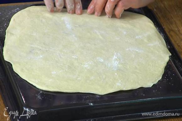 Обратную сторону противня смазать оливковым маслом и равномерно распределить раскатанное тесто.