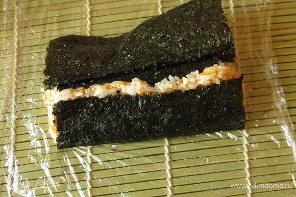 На один из скатов риса вставляем белый ролл. Поднимаем один край листа нори, прижимаем. Закрываем второй скат риса.