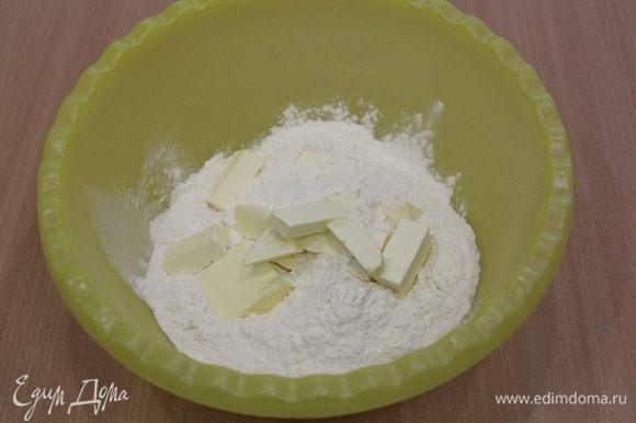В миску просеять муку и перемешать ее с сахаром и солью, добавить холодное масло, перемешать быстро руками до состояния крошки.