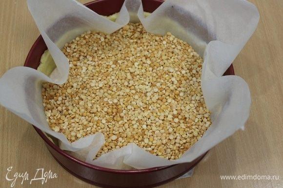 Нагрейте духовку до 170–180°C. Достать тесто из холодильника, застелить бумагой для выпечки, насыпать горох или фасоль. Отправляем тесто запекаться. Через 15 минут уберите груз и оставьте тесто еще на 10–15 минут, до легкой румяности дна.