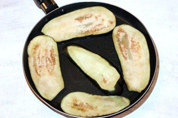 Разогреваем на сковороде растительное масло и обжариваем пластины баклажана.