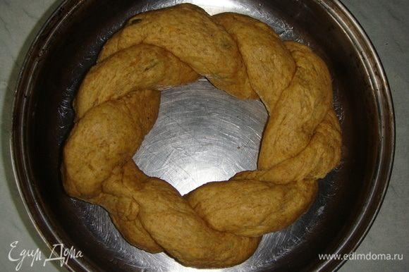 Разделить тесто на две части. Скатать колбаски и переплести их между собой, концы соединить. Выложить в смазанную маслом форму и оставить в теплом месте на 20 минут.