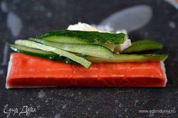 Лист рисовой бумаги замочить на 5 минут в теплой воде. Затем выложить его на тарелку, на него — крабовую палочку, чайную ложку творожного сыра и несколько соломок огурца.