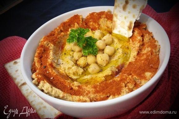 Готовый хумус переложить в пиалу, посыпать сладкой красной паприкой и полить оливковым маслом. По желанию добавить свежую зелень.