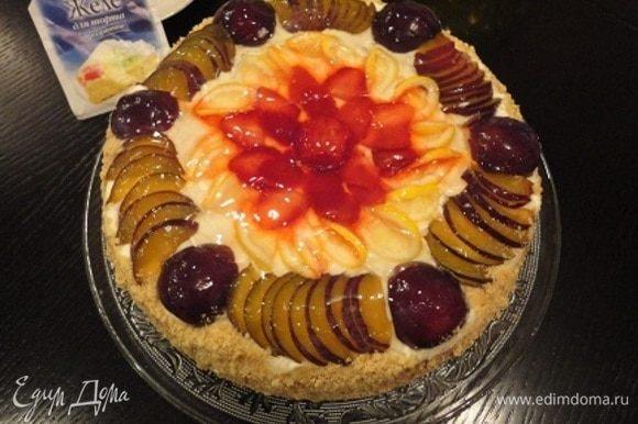 Верхний корж украсить оставшейся сливой и любимыми ягодами или фруктами. Желе для торта ТМ HAAS развести в соответствии с инструкцией на пакетике и залить торт. Бока украсить крошкой из печенья.
