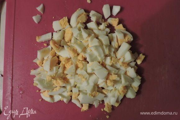 Сварить яйца вкрутую, порезать и добавить в салатник.