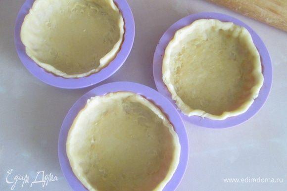 Холодное тесто разделить на равные кусочки, раскатать в тонкий пласт и выложить в формочки. В дно и бока формы аккуратно вдавить тесто, убрать излишки.