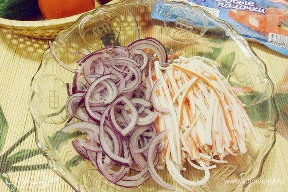 В салатник выложить нарезанные крабовые палочки и лук.