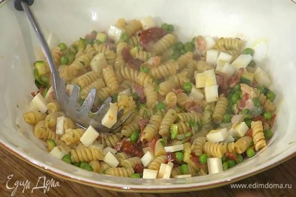 Готовую пасту посыпать измельченной мятой, перемешать и переложить на блюдо, затем посыпать нарезанным козьим сыром и еще раз перемешать, сверху сбрызнуть оставшимся оливковым маслом.